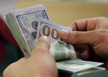 Un cliente cuenta billetes de dólar en un banco en El Cairo, Egipto. 10 de marzo de 2016. El dólar se fortalecía el martes hasta tocar máximos de dos semanas frente una cesta de divisas importantes, con los inversores a la espera del reporte de empleo que publicará el viernes Estados Unidos y que podría ofrecer pistas sobre el futuro de las tasas de interés de la Reserva Federal. REUTERS/Amr Abdallah Dalsh/File Photo