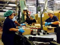 Trabajadores empacando frascos de salsa en la planta de Chelten House Products en Bridgeport, Nueva Jersey. 27 de julio de 2015. La actividad fabril en Estados Unidos se contrajo en agosto por primera vez en seis meses debido a una caída de los nuevos pedidos y de la producción, pero un nivel bajo de despidos seguía apuntando a un repunte del crecimiento económico en el tercer trimestre. REUTERS/Jonathan Spicer