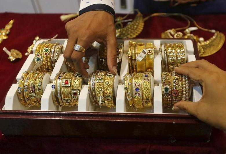 A salesman helps a customer (R) to select gold bangles at a jewelry showroom in Mumbai, India, May 21, 2015. REUTERS/Shailesh Andrade/File Photo