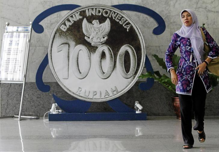 A woman walks past a poster of a one thousand rupiah coin inside Indonesia's central bank, Bank Indonesia, in Jakarta, Indonesia July 21, 2016. REUTERS/Iqro Rinaldi