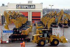 Workers walk past Caterpillar excavator machines at a factory in Gosselies February 28, 2013.   REUTERS/Eric Vidal/File Photo