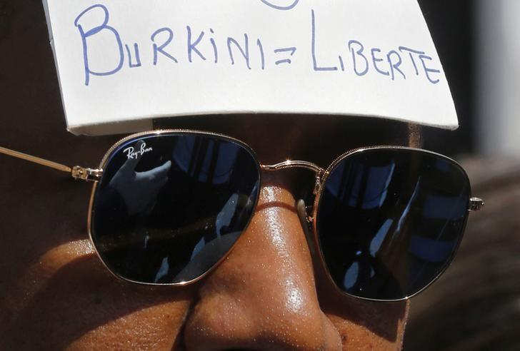 A man wears a placard with the message, ''Burkini = Liberty'' outside the Conseil d'Etat after France's highest administrative court suspended a ban on full-body burkini swimsuits that has outraged Muslims and opened divisions within the government, pending a definitive ruling, in Paris, France, August 26, 2016. REUTERS/Regis Duvignau/Files