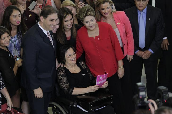 Brazil's President Dilma Rousseff (in red) poses with women's rights activist Maria da Penha during the launch of the ''Woman: Living without Violence'' program at the Planalto Palace in Brasilia March 13, 2013. REUTERS/Ueslei Marcelino