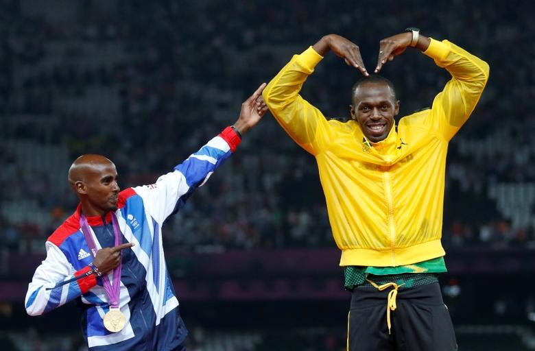 Jamaica's Usain Bolt (R) celebrates with Britain's Mo Farah on the podium after each receiving gold medals, Bolt for men's 4x100m relay and Farah for men's 5000m, at the victory ceremony at the London 2012 Olympic Games at the Olympic Stadium in Britain August 11, 2012. REUTERS/Eddie Keogh