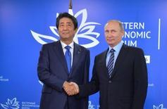 Президент России Владимир Путин (справа) пожимает руку премьеру Японии Синдзо Абэ на встрече во Владивостоке 2 сентября 2016 года. Абэ сказал после переговоров с  Путиным в пятницу, что Япония и Россия способны добиться прогресса в разрешении территориального спора,  омрачающего отношения более 70 лет. Кремль остудил ожидания. Sputnik/Kremlin/Alexei Druzhinin/via REUTERS