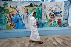 A nun belonging to the global Missionaries of Charity walks past a mural at Prem Dan, a home for the destitute and old run by the Missionaries of Charity, ahead of Mother Teresa's canonisation ceremony, in Kolkata, India September 1, 2016. REUTERS/Rupak De Chowdhuri