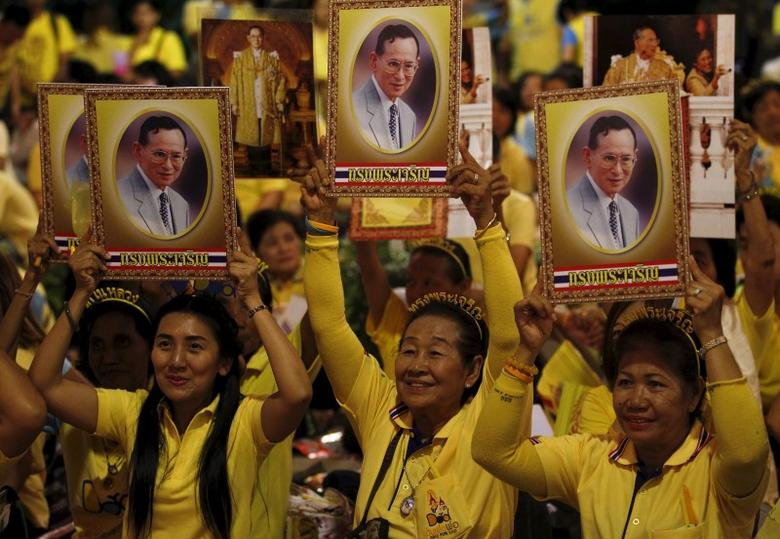 Well-wishers hold portraits of Thailand's King Bhumibol Adulyadej at Siriraj hospital, where a group has gathered to mark his 88th birthday, in Bangkok, Thailand, December 5, 2015. REUTERS/Chaiwat Subprasom