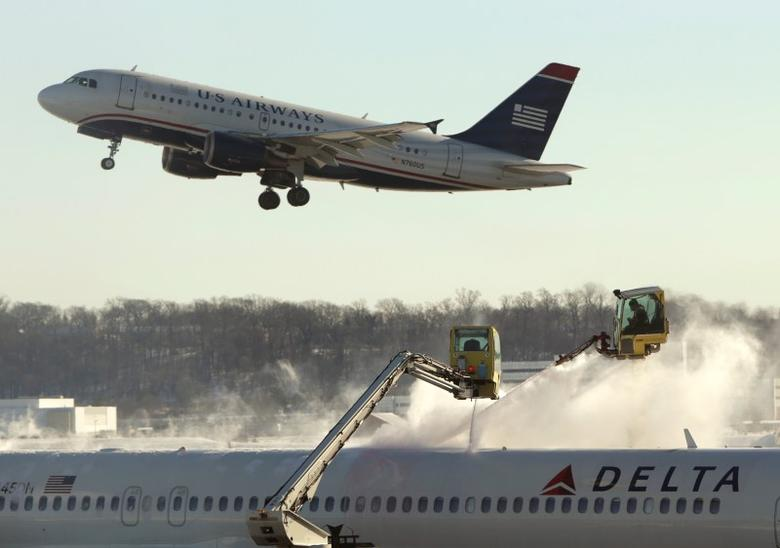 A Delta jetliner (bottom) is de-iced while a US Airways jet takes off at Reagan National Airport in Washington January 3, 2014.REUTERS/Gary Cameron