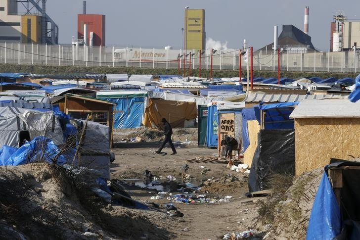 A migrant walks past makeshift shelters in the northern area on the final day of the dismantlement of the southern part of the camp called the 'Jungle'' in Calais, France, March 16, 2016. REUTERS/Pascal Rossignol/File Photo