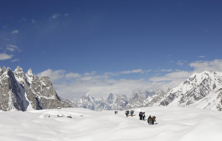 Trekkers and porters hike down the Baltoro glacier in the Karakoram mountain range in Pakistan September 7, 2014. REUTERS/Wolfgang Rattay/Files