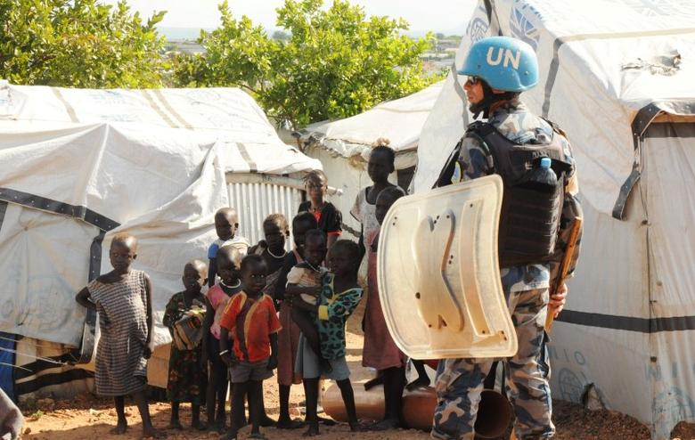 A U.N. peacekeeper stands guard near children displaced in recent fighting, during a visit by the United Nations Security Council, delegation to the UN House in Jebel, near South Sudan's capital Juba, September 3, 2016. REUTERS/Jok Solomun