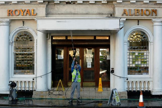 A worker hoses down the entrance to a hotel in Brighton southern England January 6, 2015. REUTERS/Luke MacGregor