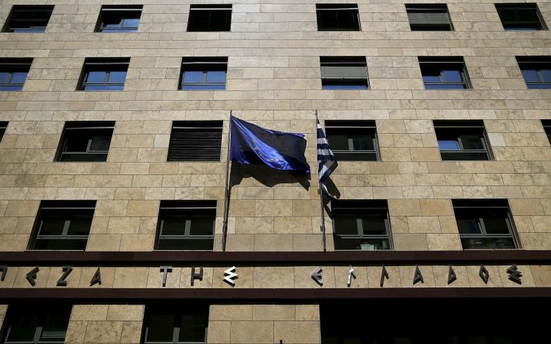 A European Union flag (L) flutters next to a Greek flag on the facade of the Bank of Greece headquarters in Athens April 14, 2015. REUTERS/Alkis Konstantinidis