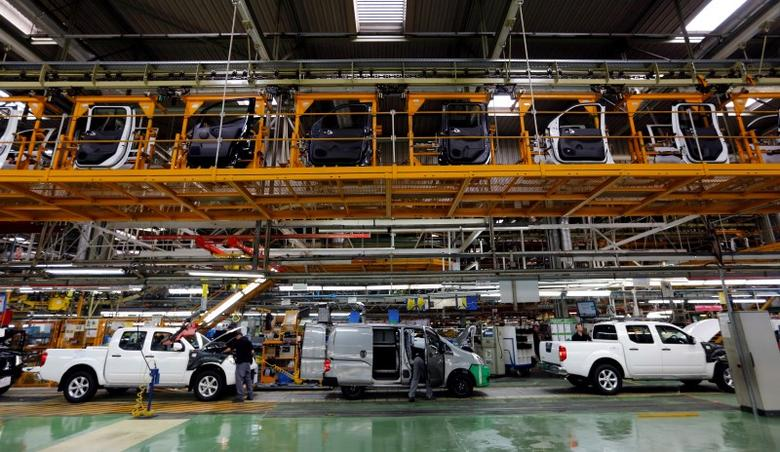 Nissan Motor staff work on the assembly line at the Zona Franca Nissan factory near Barcelona May 5, 2014. REUTERS/Albert Gea