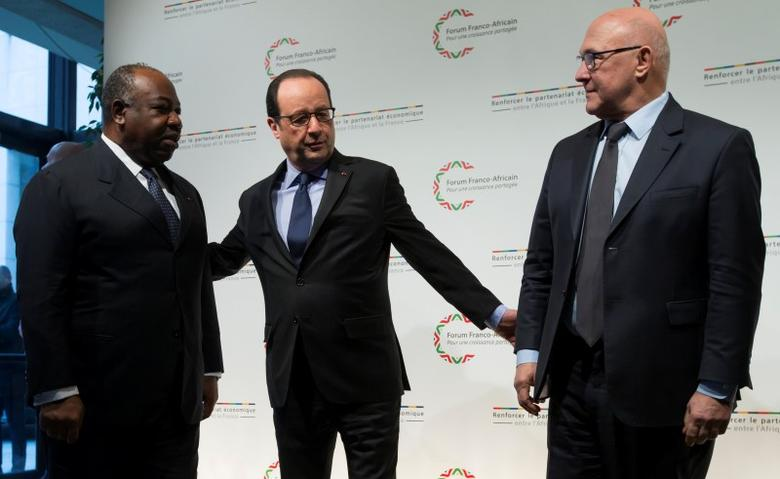 French President Francois Hollande (C) and French Finance Minister Michel Sapin (R) greet Gabon's President Ali Bongo as he arrives to attend the Franco-African Forum at the Bercy Finance Ministry in Paris, February 6, 2015.  REUTERS/Ian Langsdon/Pool/Files
