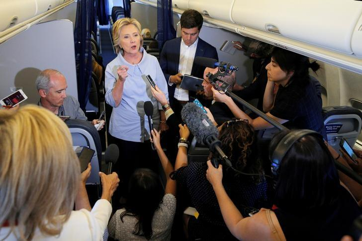 U.S. Democratic presidential candidate Hillary Clinton answers questions from reporters on her campaign plane enroute to a campaign stop in Moline, Illinois, United States September 5, 2016.  REUTERS/Brian Snyder