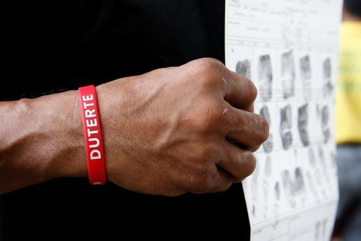 A man, who admitted to be a drug user, wears an election campaign armband of President-elect Rodrigo Duterte, as he shows a copy of his fingerprints to a police officer (not pictured) at a police camp, after more than 700 people surrendered to policemen and local government officials in Quezon city, Metro Manila, Philippines June 24, 2016.  REUTERS/Erik De Castro/File Photo