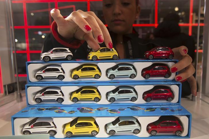 An employee installs new 2014 Renault Twingo miniatures at the L'Atelier Renault, the international showroom of French carmaker Renault, in Paris December 16, 2014. REUTERS/Philippe Wojazer/Files