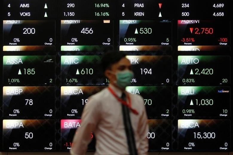 An employee walks in front of an electronic board at the Indonesia Stock Exchange (IDX) in Jakarta, Indonesia August 22, 2016.  Picture taken August 22, 2016. REUTERS/Iqro Rinaldi