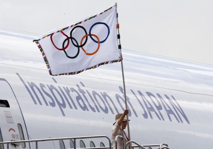 Tokyo governor Yuriko Koike waves the Olympic flag as she walks out of a plane during a ceremony to mark the arrival of the Olympic flag at Haneda airport in Tokyo, Japan, August 24, 2016.   REUTERS/Kim Kyung-Hoon/Files