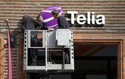 Рабочие устанавливают вывеску на салоне связи TeliaSonera в Стокгольме. 12 мая 2011 года. Скандинавский телекоммуникационный оператор Telia Company сообщил о продаже своей доли в таджикском операторе Tcell в рамках своего плана полностью уйти с центральноазиатских рынков. REUTERS/Bob Strong