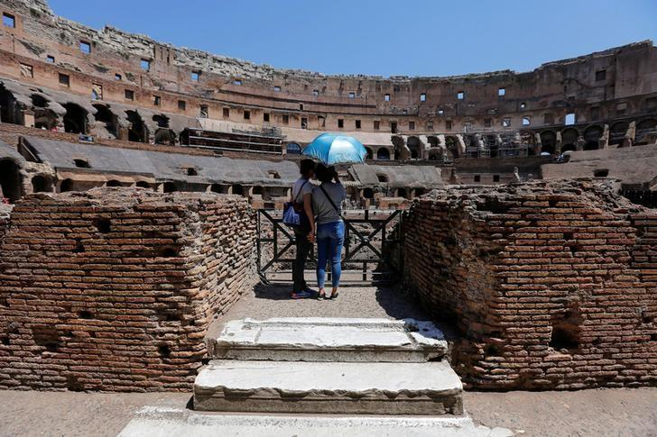 Tourists use an umbrella to protect themselves from the sun as they visit the Colosseum in Rome, Italy, July 1, 2016. REUTERS/Alessandro Bianchi/File Photo
