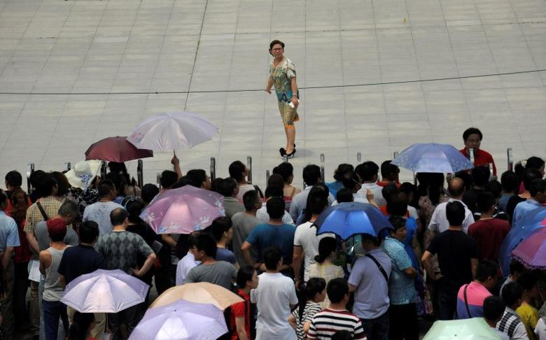 A teacher looks back at family members waiting outside a high school during the national college entrance exam in Wuhan, Hubei province, June 7, 2014. REUTERS/Stringer