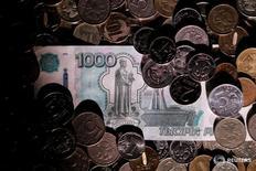 Рублевые монеты  и купюра 7 июня 2016 года. Рубль вырос в четверг вслед за нефтяными котировками, обновив трехнедельные максимумы на фоне сильнейшего с апреля 1985 года падения недельных запасов нефти в США, а также на фоне снижения курса доллара на форексе. REUTERS/Maxim Zmeyev/Illustration