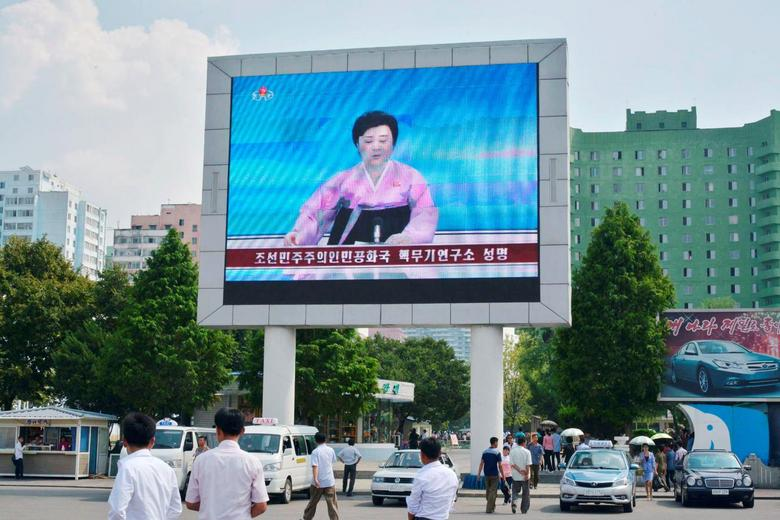 North Koreans walk past near a huge screen broadcasting the government's announcement on North Korea's fifth nuclear test in Pyongyang, North Korea, in this photo released by Kyodo September 9, 2016. Mandatory credit Kyodo/via REUTERS
