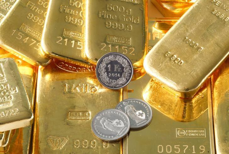 Gold bars from the vault of a bank and Swiss one franc coins are seen in this illustration picture taken in Zurich November 20, 2014.  REUTERS/Arnd Wiegmann/Files