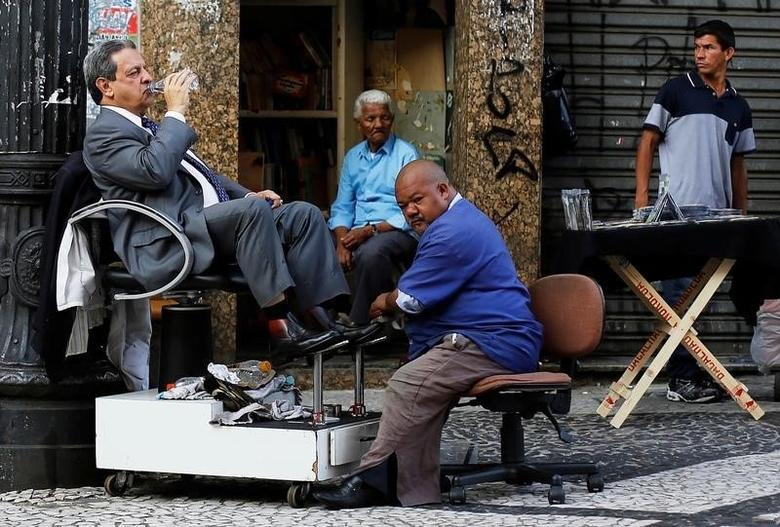 A customer drinks a bottle of water as his shoes are polished by a shoe shiner on a street in downtown Sao Paulo April 8, 2014. REUTERS/Nacho Doce/File Photo
