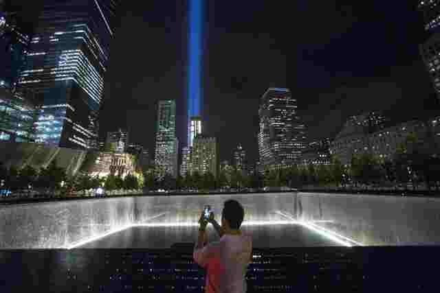 A man takes a photo at the 9/11 Memorial and Museum near the Tribute in Light in Lower Manhattan, New York, September 9, 2015. REUTERS/Andrew Kelly/File Photo