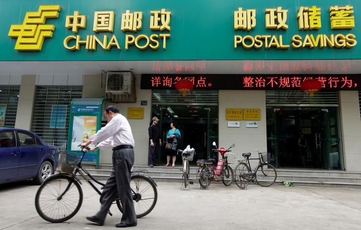 A man pushes his bicycle past a branch of China Post's Postal Savings Bank of China in Wuhan, Hubei province May 4, 2012. REUTERS/Stringer/File Photo