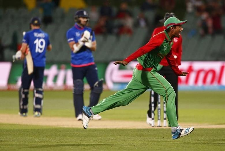 Bangladesh's Mohammad Mahmudullah runs in celebration past the last two English batsman on the pitch Chris Woakes (L) and James Anderson after Bangladesh knocked England out of the tournament following their Cricket World Cup match in Adelaide, March 9, 2015.     REUTERS/David Gray