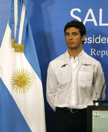 Argentine driver Jose Maria Lopez poses next to an Argentine flag during a news conference in Buenos Aires January 25, 2010.      REUTERS/Enrique Marcarian