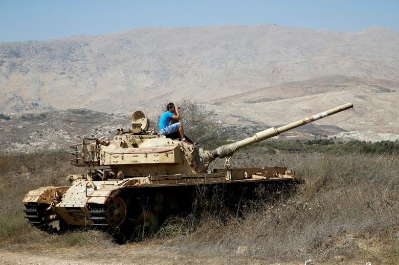 A man sits on an old tank as he watches fighting taking place in Syria as seen from the Israeli side of the border fence between Syria and the Israeli-occupied Golan Heights September 11, 2016. REUTERS/Baz Ratner
