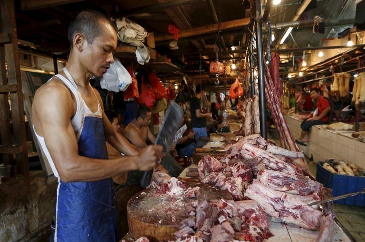 A butcher cuts meat at his stall at a traditional market in Jakarta, Indonesia, September 9, 2015.  REUTERS/Nyimas Laula