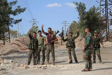 Солдаты, преданные Башару Асаду, показывают знаки победы после взятия районов в Алеппо/ Сирийская армия сообщила во вторник, что сбила израильские военный самолёт и беспилотник в Сирии после того, как Израиль атаковал позиции армии на юге страны, передают государственные СМИ.  SANA/Handout via REUTERS