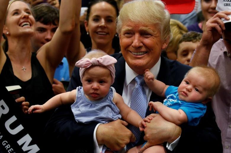 Republican presidential nominee Donald Trump holds babies at a campaign rally in Colorado Springs, Colorado, U.S., July 29, 2016. REUTERS/Carlo Allegri - RTSKBR1