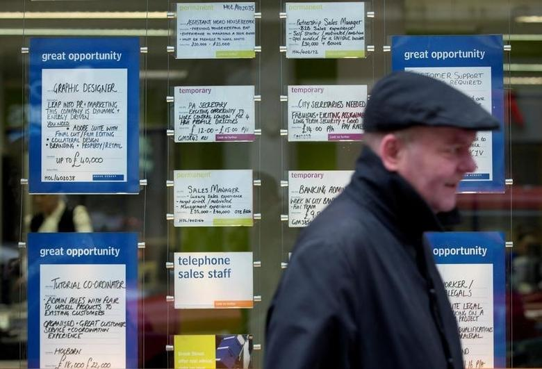 A man walks past job advertisements in the window of a recruitment office in central London February 19, 2014.   REUTERS/Neil Hall/File Photo