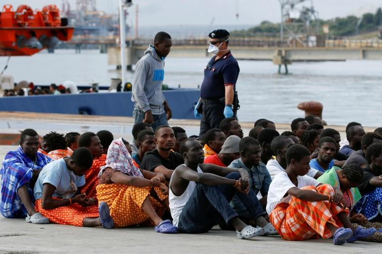 Migrants sit after they disembarked from the vessel Topaz Responder in the Sicilian harbour of  Augusta, Italy  September 7, 2016. REUTERS/Antonio Parrinello