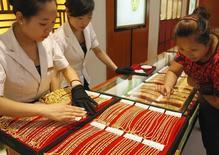 Женщина выбирает золотые украшения в ювелирном магазине в китайском городе Хуайбэй. 5 августа 2010 года. ВТБ сообщил во вторник, что планирует поставить 15-20 тонн золота в Китай в течение 12 месяцев и затем увеличивать поставки в зависимости от спроса там. REUTERS/Stringer