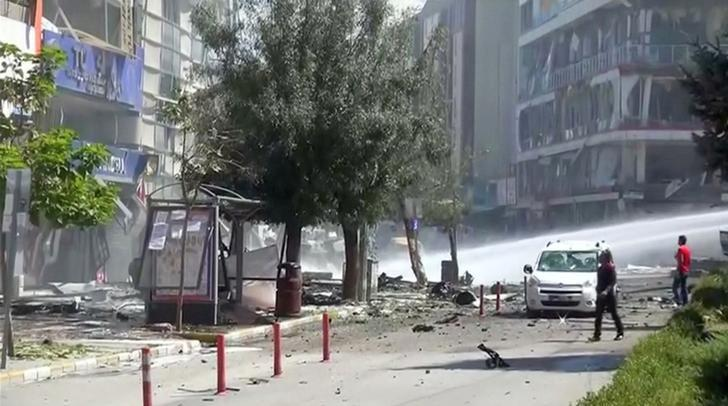 A water cannon sprays in front of damaged buildings and vehicles after suspected Kurdish militants detonated a car bomb near local government offices in Turkey's southeastern city of Van September 12, 2016 in this still image taken from video. REUTERS/via Reuters TV