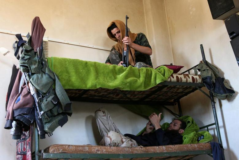 Rebel fighters rest on a double bed in Jubata al-Khashab, in Quneitra countryside, Syria September 11, 2016. REUTERS/Alaa Al-Faqir