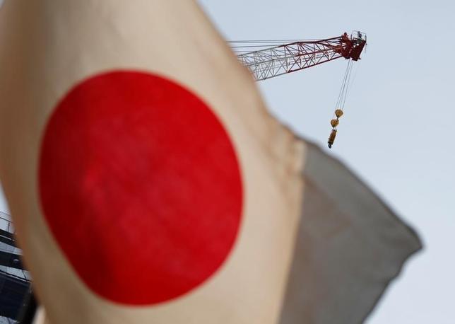 9月13日、格付け会社フィッチのソブリン格付け担当責任者、ジェームズ・マコーマック氏は、日本の経験を踏まえると、先進国がいくら財政出動に踏み切ってもその効果は長続きせず、借金だけが膨らむ恐れがあるとの見方を示した。写真は都内で8月、日本の国旗と工事現場のクレーン車(2016年 ロイター/Kim Kyung-Hoon)