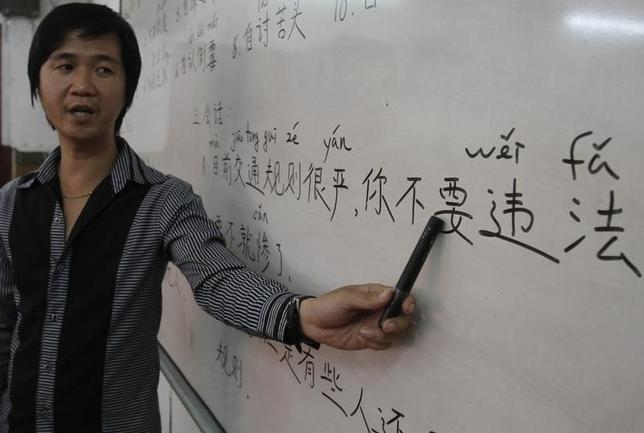 9月13日、中国では、公用語の北京語を話す国民の割合がここ15年ほどで大幅に増えたものの、少数民族が住む辺境地域などでは普及がさほど進んでいない。写真は北京語の教師。2012年7月撮影(2016年 ロイター/Samrang Pring)