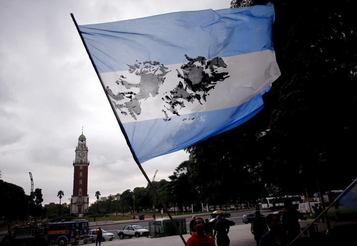 A man waves an Argentine flag with an image of the Falkland Islands, known to Argentines as 'Malvinas', in front of the Tower of the English during the commemoration of the 34th anniversary of the 1982 war between Britain and Argentina over the Falklands, at the memorial dedicated to Argentine soldiers who died during the conflict in downtown Buenos Aires April 2, 2016. REUTERS/Marcos Brindicci/File Photo