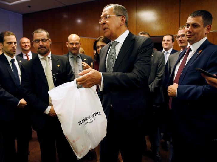 Russian Foreign Minister Sergei Lavrov delivers vodka to reporters awaiting a late night press conference along with U.S. Secretary of State John Kerry and in Geneva, Switzerland where two discussed the crisis in Syria September 9, 2016.  REUTERS/Kevin Lamarque