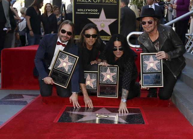 Members of Mexican rock band Mana (L-R) Sergio Vallin, Juan Calleros, Alex Gonzalez and Fher Olvera pose by their star after it was unveiled on the Hollywood Walk of Fame in Los Angeles, California, February 10, 2016.   REUTERS/Mario Anzuoni