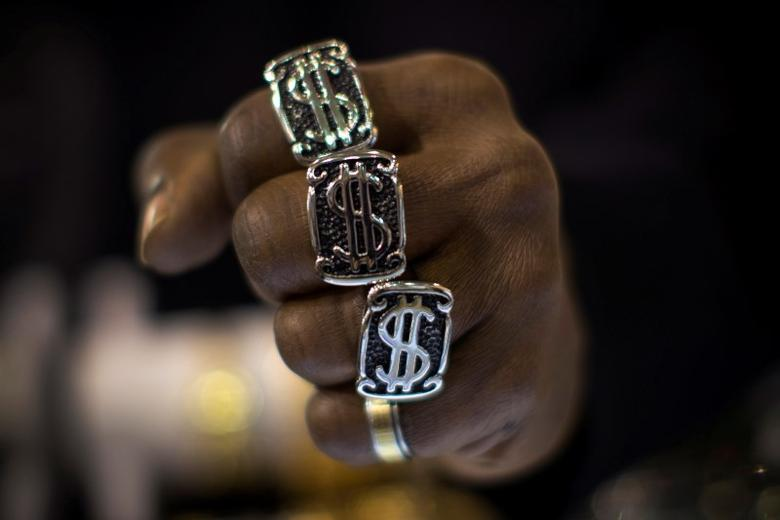 A man wears U.S. dollar sign rings in a jewellery shop in Manhattan in New York City November 6, 2014.   REUTERS/Mike Segar/File Photo